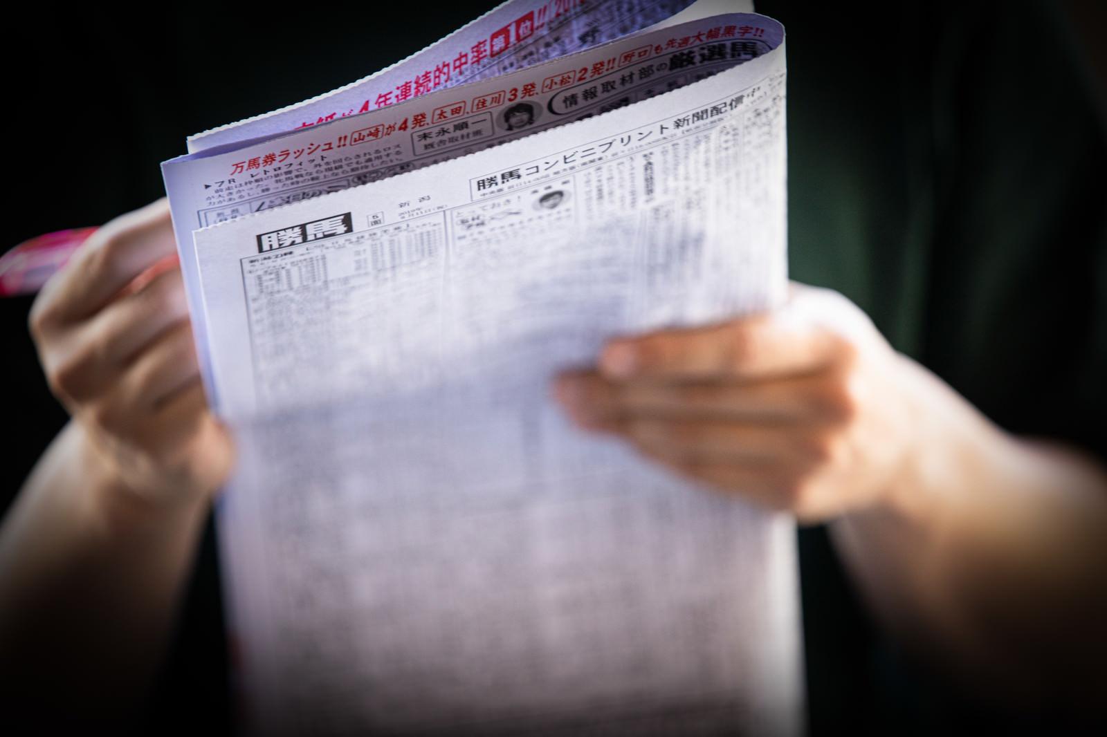 「競馬新聞を買って予想中」の写真