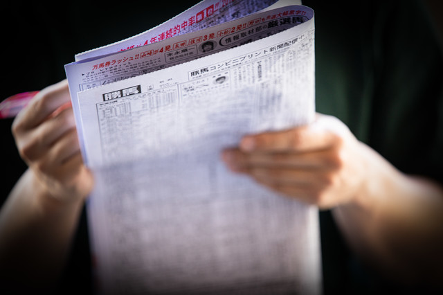 競馬新聞を買って予想中の写真