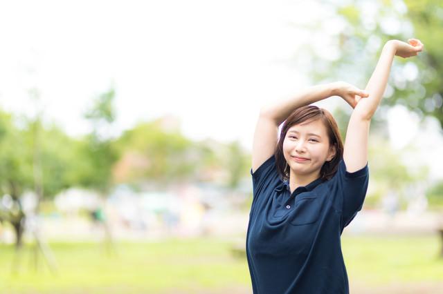 公園で伸びをする女性の写真