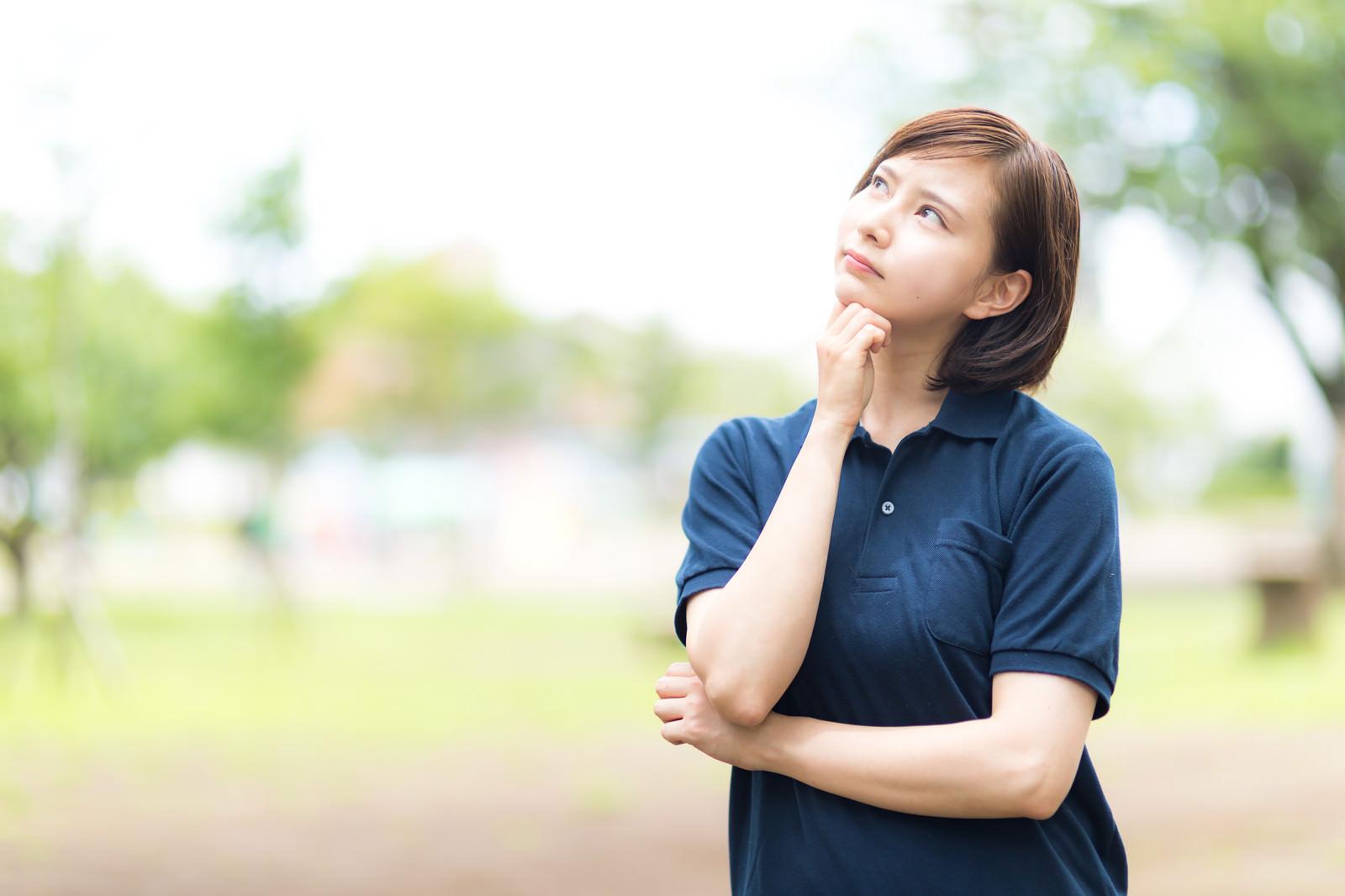 「空を見上げて考え込むヘルパーの女性」の写真[モデル:yumiko]