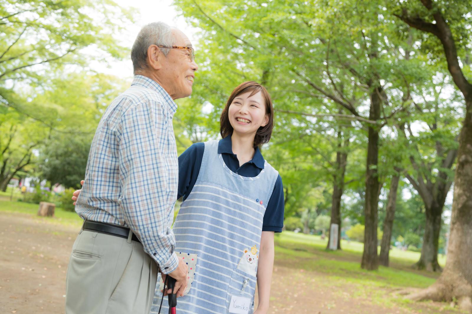 「高齢者の男性と公園散歩を楽しむ介護士の女性」の写真[モデル:まーちゃん yumiko]