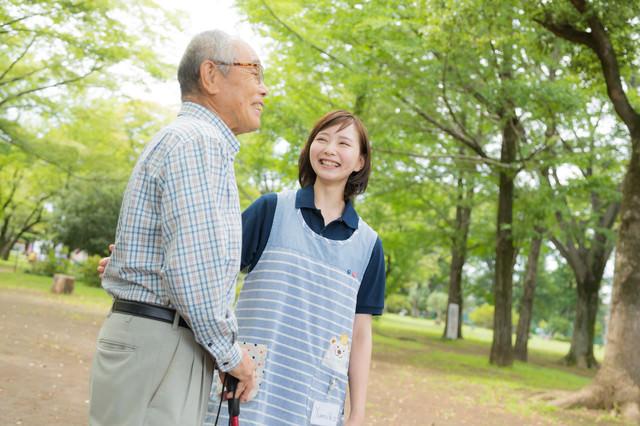 高齢者の男性と公園散歩を楽しむ介護士の女性の写真