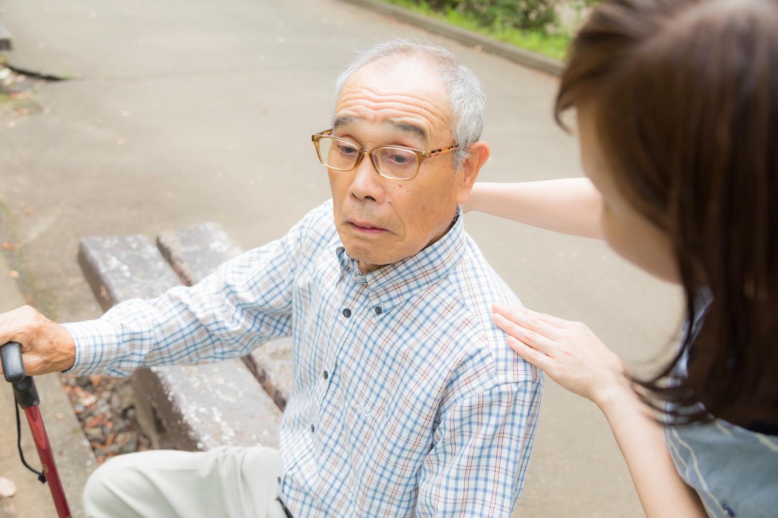 「疲れてベンチに座る老人に声をかける女性」の写真[モデル:まーちゃん yumiko]