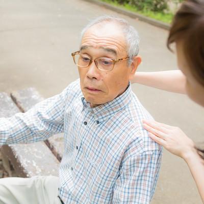 疲れてベンチに座る老人に声をかける女性の写真