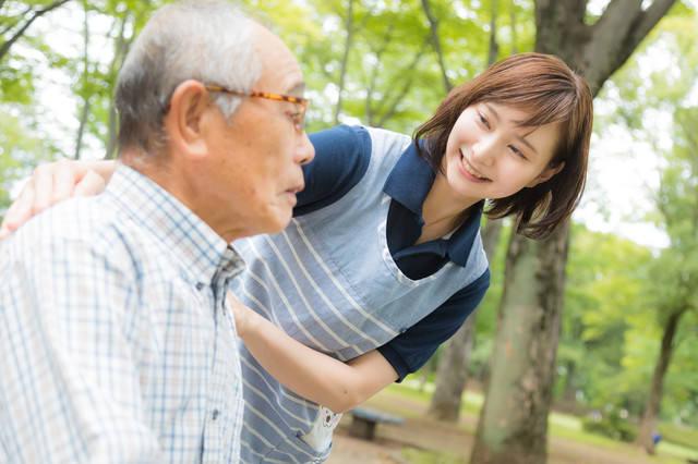 元気がないお爺さんに声をかける介護士の女性の写真