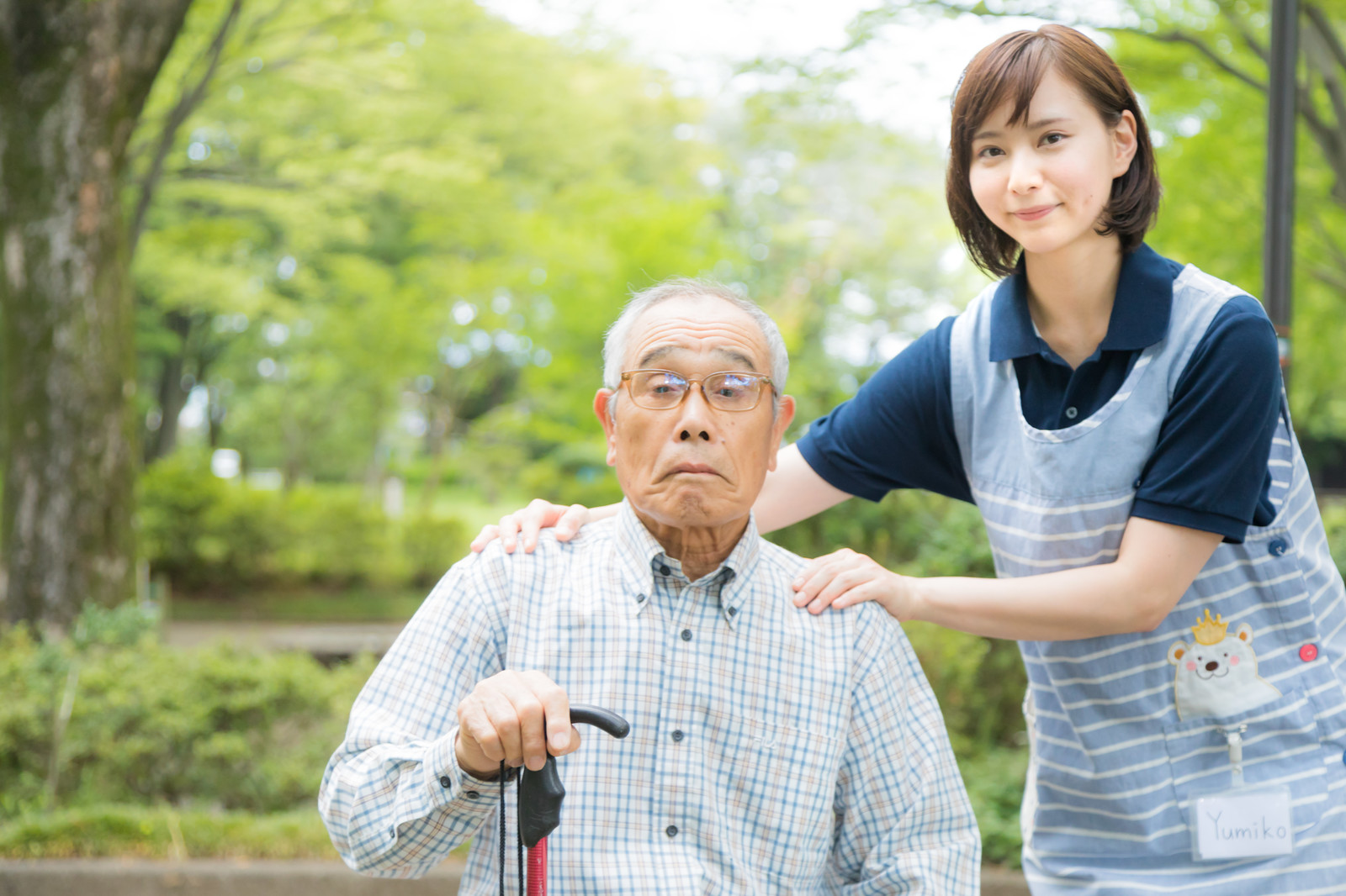 「介護士さんと記念撮影するお爺さん」の写真[モデル:まーちゃん yumiko]