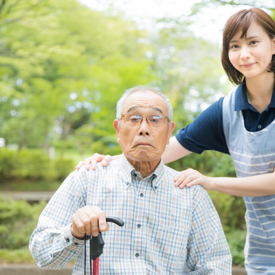 介護士さんと記念撮影するお爺さんの写真