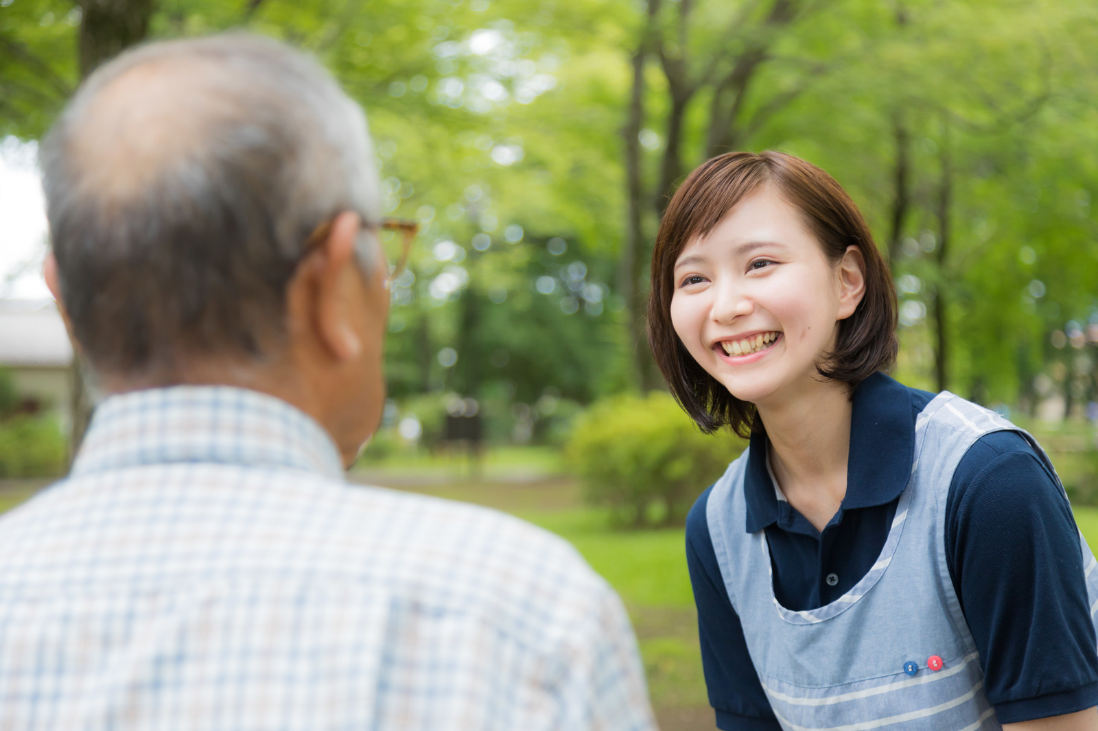 「お爺さんの昔話を笑顔で聞く介護士の女性」の写真[モデル:まーちゃん yumiko]