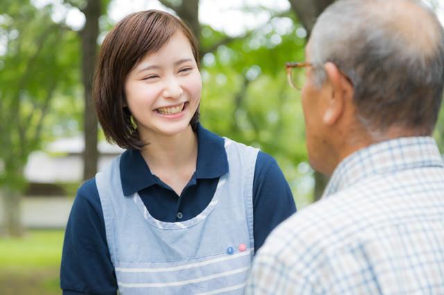 笑顔で高齢者と接する介護士の女性の写真