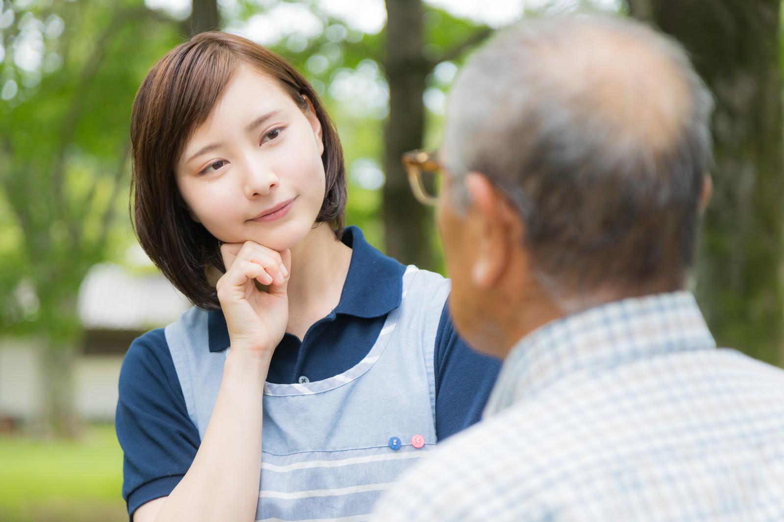 「頑固な老人と対話する介護士の女性」の写真[モデル:yumiko まーちゃん]