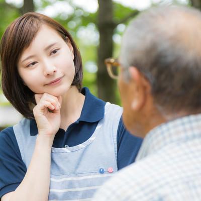 頑固な老人と対話する介護士の女性の写真