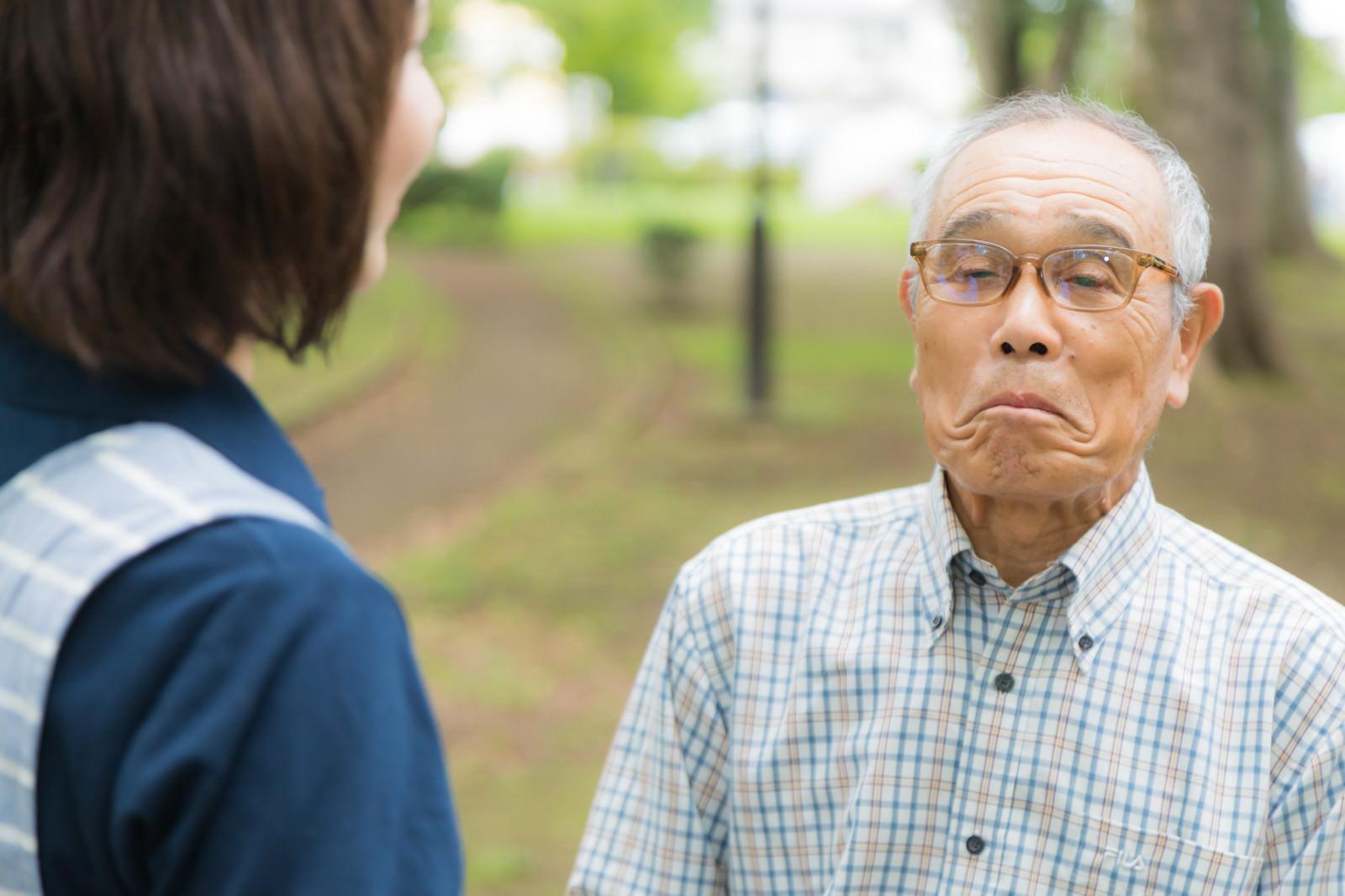 「口をへの字にして動かない高齢者と説得するヘルパー」の写真[モデル:まーちゃん yumiko]