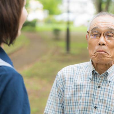 口をへの字にして動かない高齢者と説得するヘルパーの写真