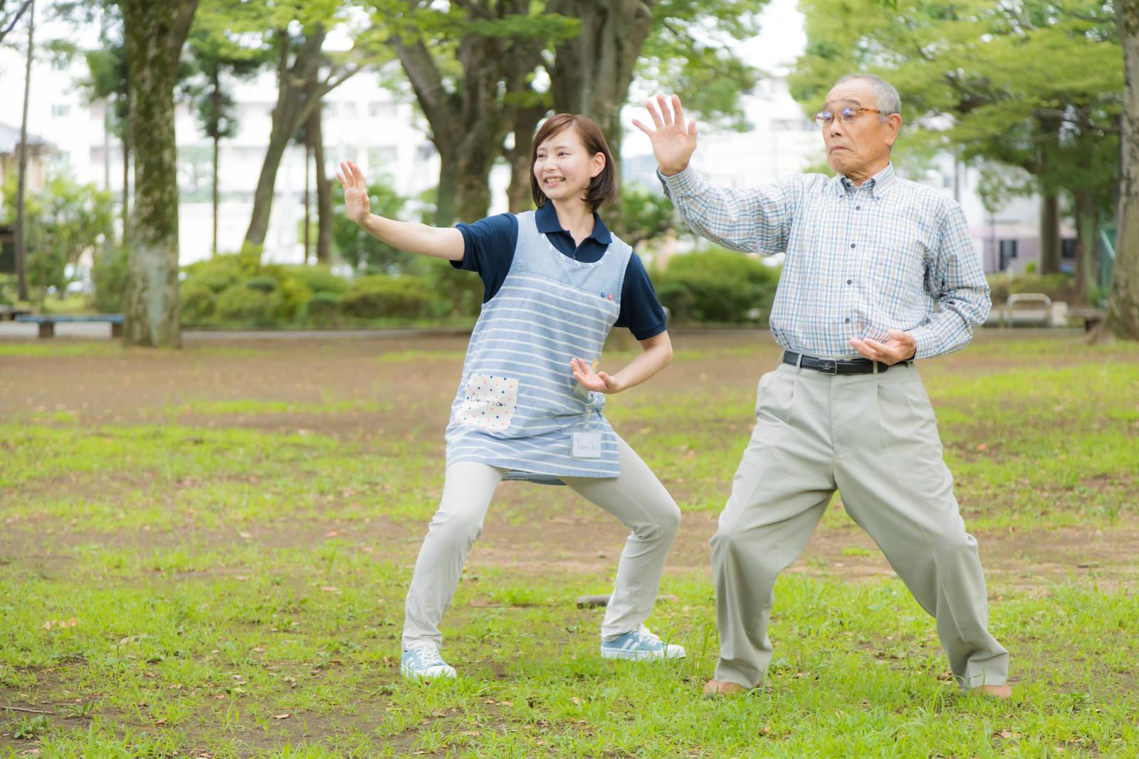 「お爺さんが毎朝日課にしている体操に付き合う介護士の女性」の写真[モデル:まーちゃん yumiko]