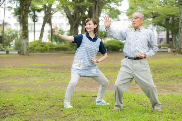 お爺さんが毎朝日課にしている体操に付き合う介護士の女性の写真