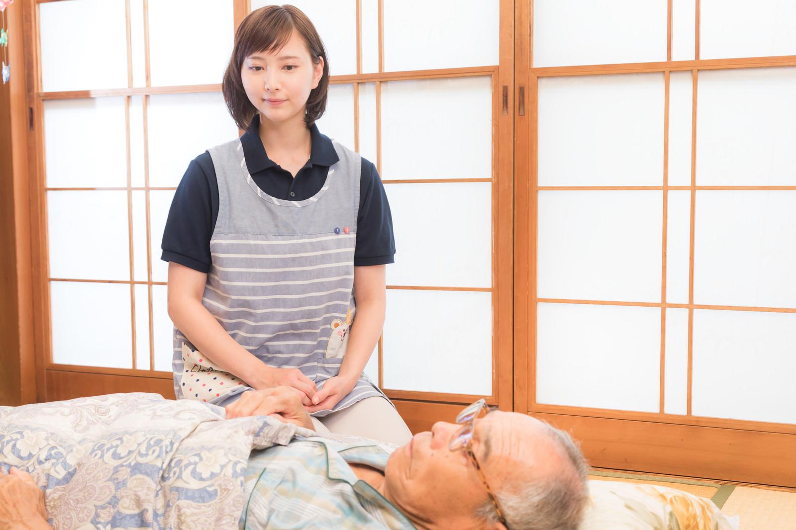 「寝たきりの高齢者を心配する介護士の女性」の写真[モデル:まーちゃん yumiko]