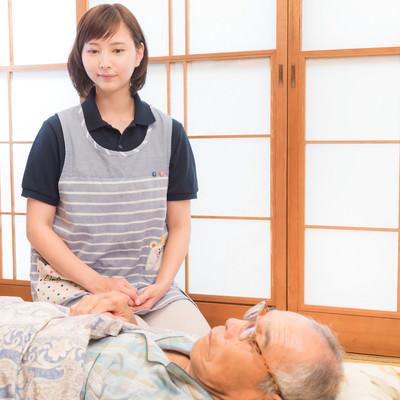 寝たきりの高齢者を心配する介護士の女性の写真