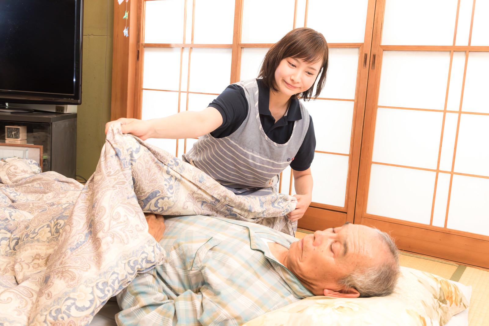 「お爺さんに布団をかぶせる介護士の女性」の写真[モデル:まーちゃん yumiko]