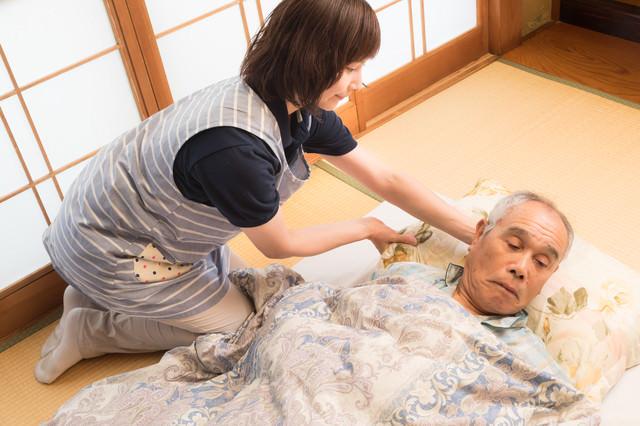 布団の上に横になった老人の枕を直す女性介護士の写真