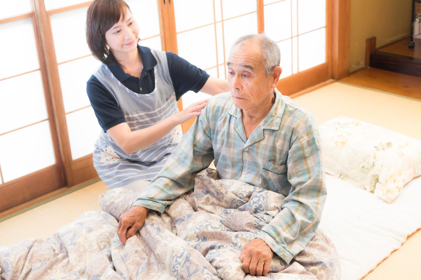 「寝たきり老人の背中をさする女性ヘルパー」の写真[モデル:yumiko まーちゃん]