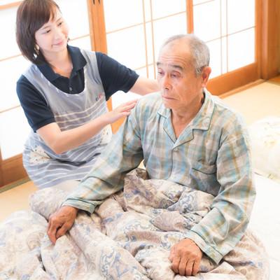寝たきり老人の背中をさする女性ヘルパーの写真