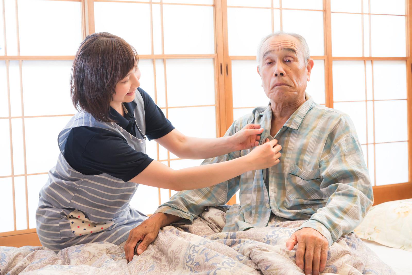 「高齢者のパジャマのボタンをつける出張介護士」の写真[モデル:まーちゃん yumiko]