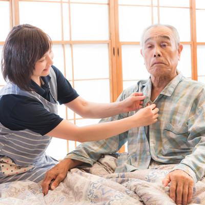 高齢者のパジャマのボタンをつける出張介護士の写真