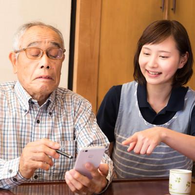 女性の介護士にスマホの使い方を教えてもらう老人の写真