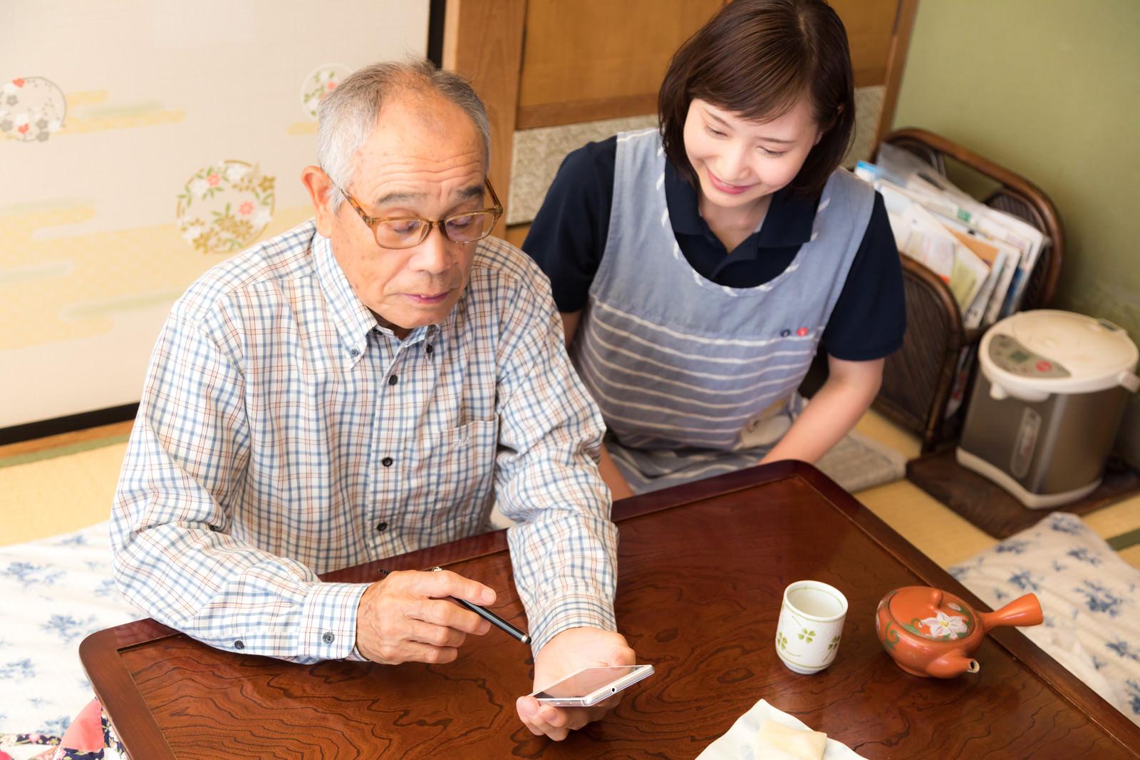 「孫とビデオチャットを楽しむお爺さんと側で教える介護士」の写真