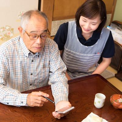 孫とビデオチャットを楽しむお爺さんと側で教える介護士の写真