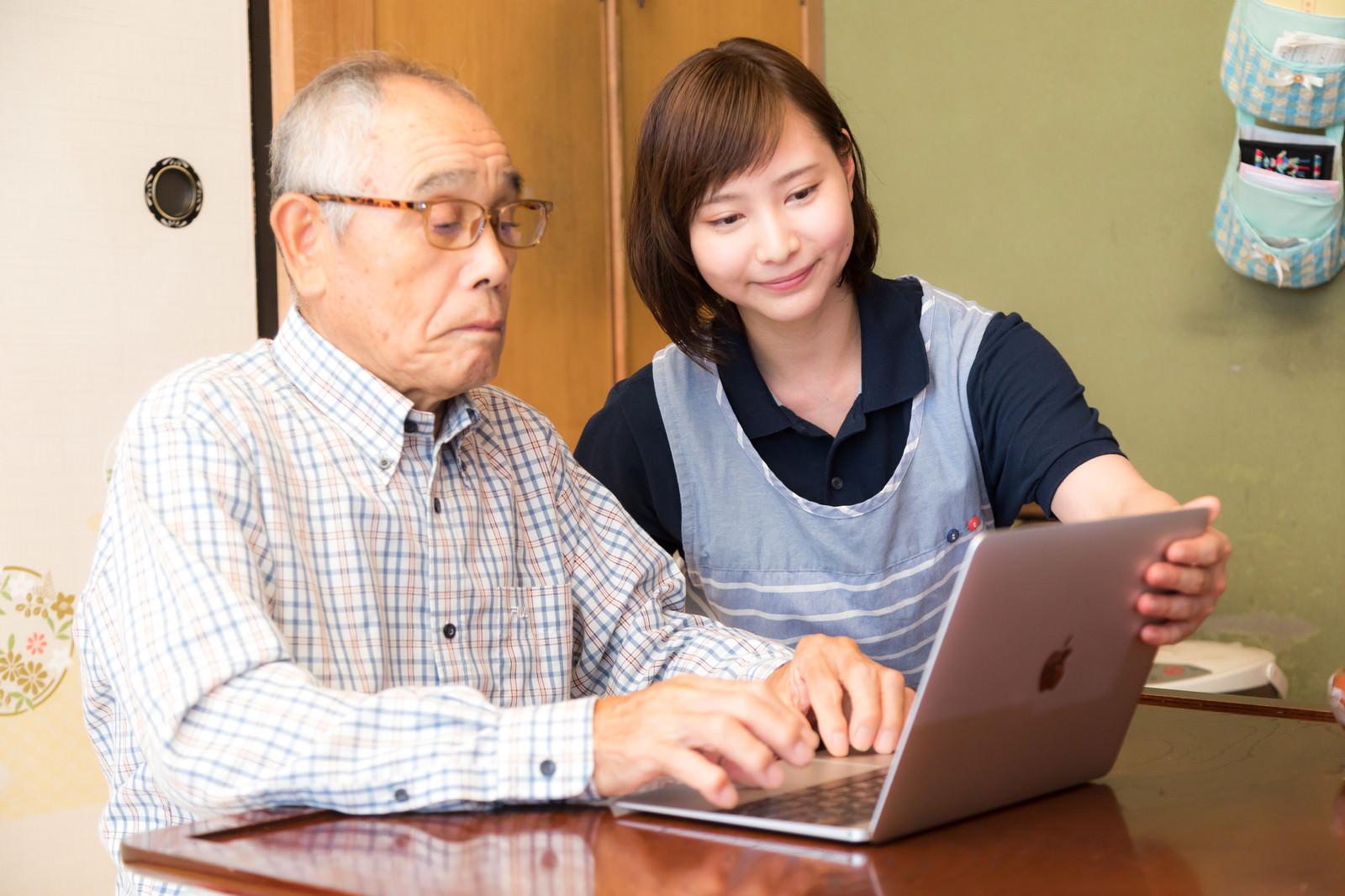 「パソコン講習中の高齢者と介護士」の写真[モデル:まーちゃん yumiko]