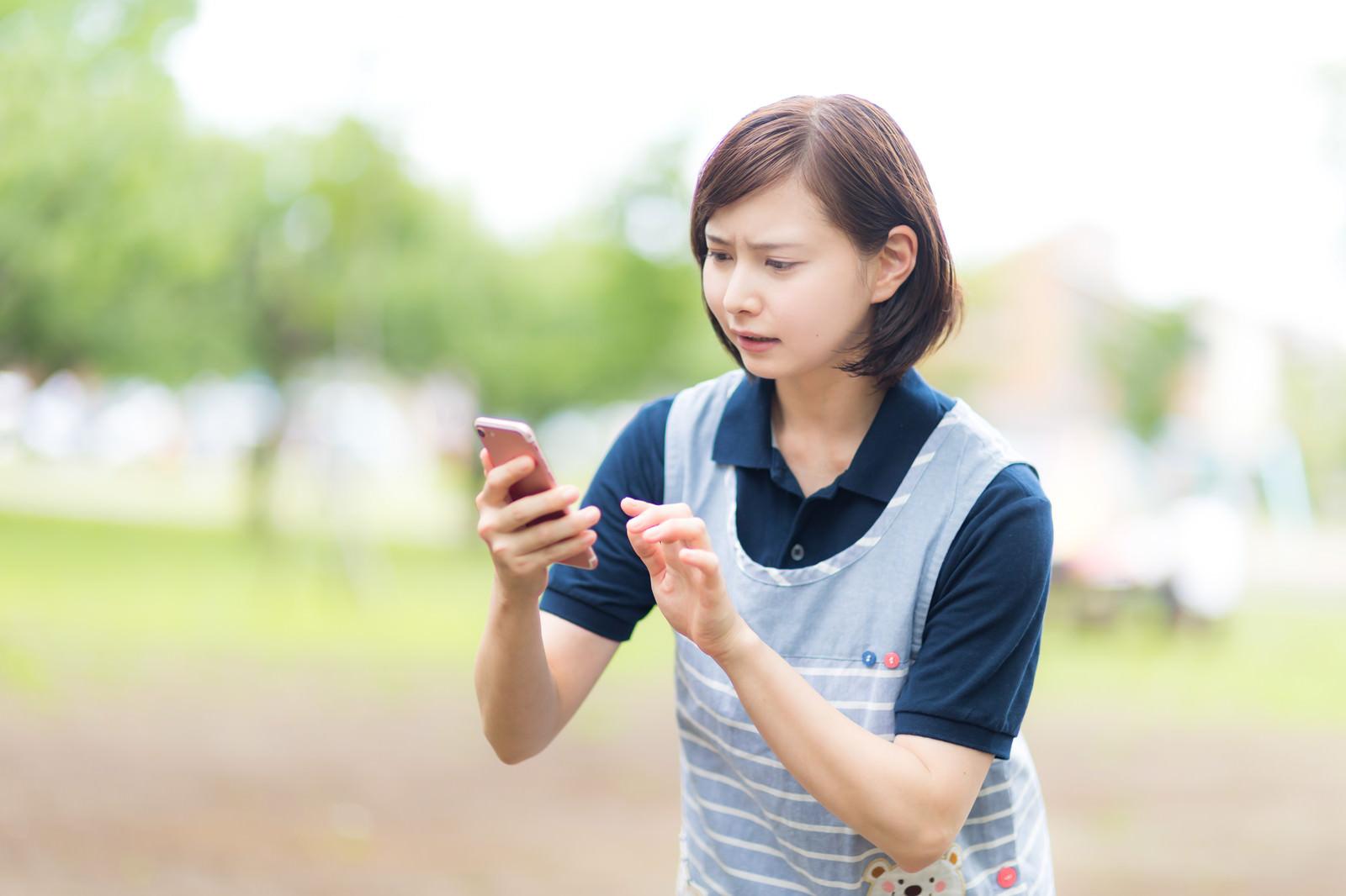 「迷子をスマホのGPSで探すエプロン姿の介護士」の写真[モデル:yumiko]
