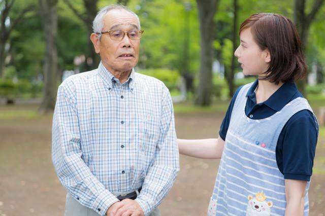 ひとりで外出してしまった老人と心配する介護士の写真