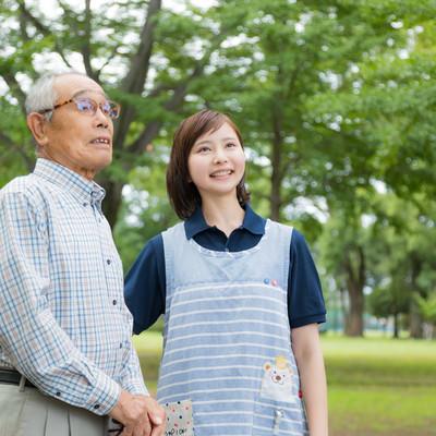 外出する高齢者と付添の介護士の写真