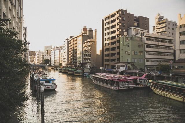 屋形船が停泊している河川と夕暮れの写真