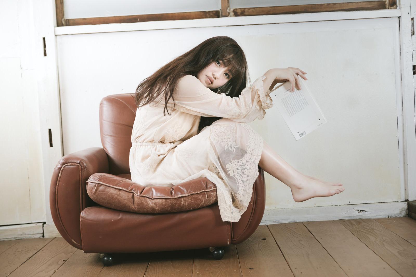 「一人掛けソファーを大胆に使う読書女子」の写真[モデル:河村友歌]