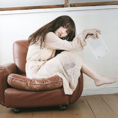 「一人掛けソファーを大胆に使う読書女子」の写真素材