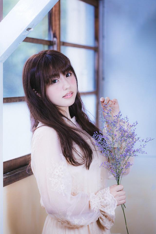 レトロな窓と質素な花を持つポートレート女子の写真