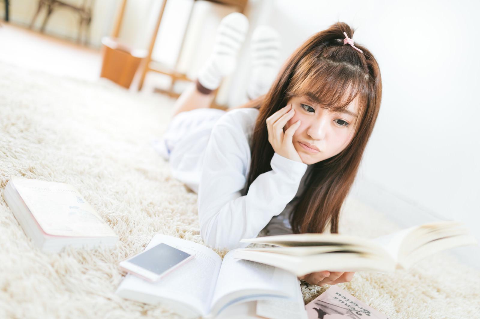 「部屋で課題の本を読む女子大生部屋で課題の本を読む女子大生」[モデル:河村友歌]のフリー写真素材を拡大