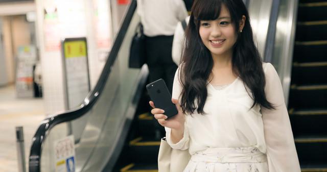 財布や定期券を出さずにスマートフォンで駅の改札を出る女性の写真