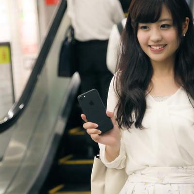「財布や定期券を出さずにスマートフォンで駅の改札を出る女性」の写真素材