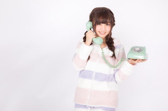 ダイヤル式の電話を片手に通話する女性の写真