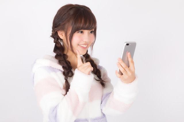 フリマアプリで出品した商品が売れて喜ぶ女性の写真