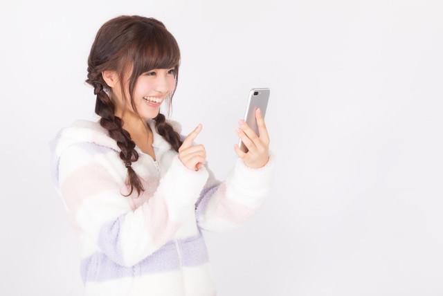 笑顔でスマホアプリを楽しむ女性の写真