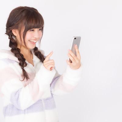 「笑顔でスマホアプリを楽しむ女性」の写真素材
