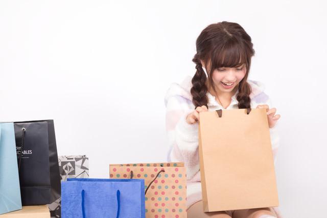 届いたプレゼントを開封して喜ぶ女性の写真