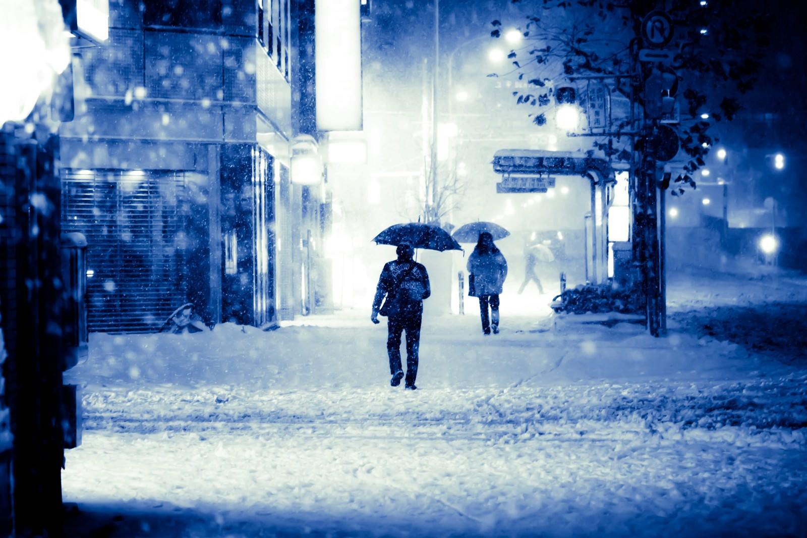 「積雪で電車が止まり傘を差して家路に向かう」の写真