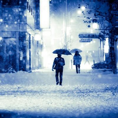 「積雪で電車が止まり傘を差して家路に向かう」の写真素材