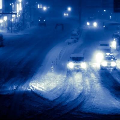 雪が降り積もる夜の幹線道路の写真