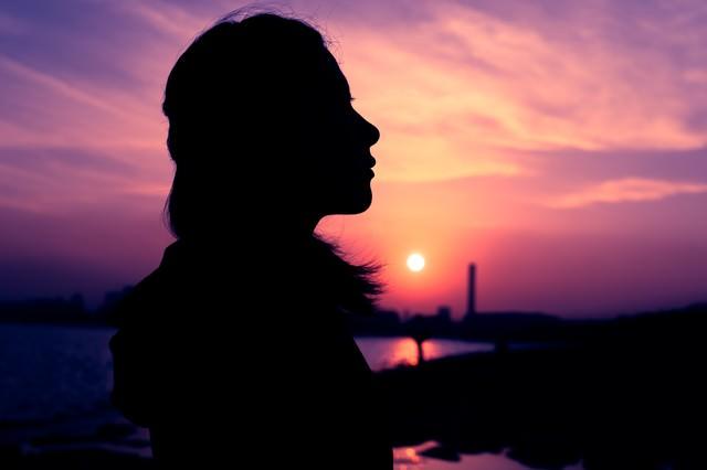 紫色の夕焼けと女性のシルエットの写真